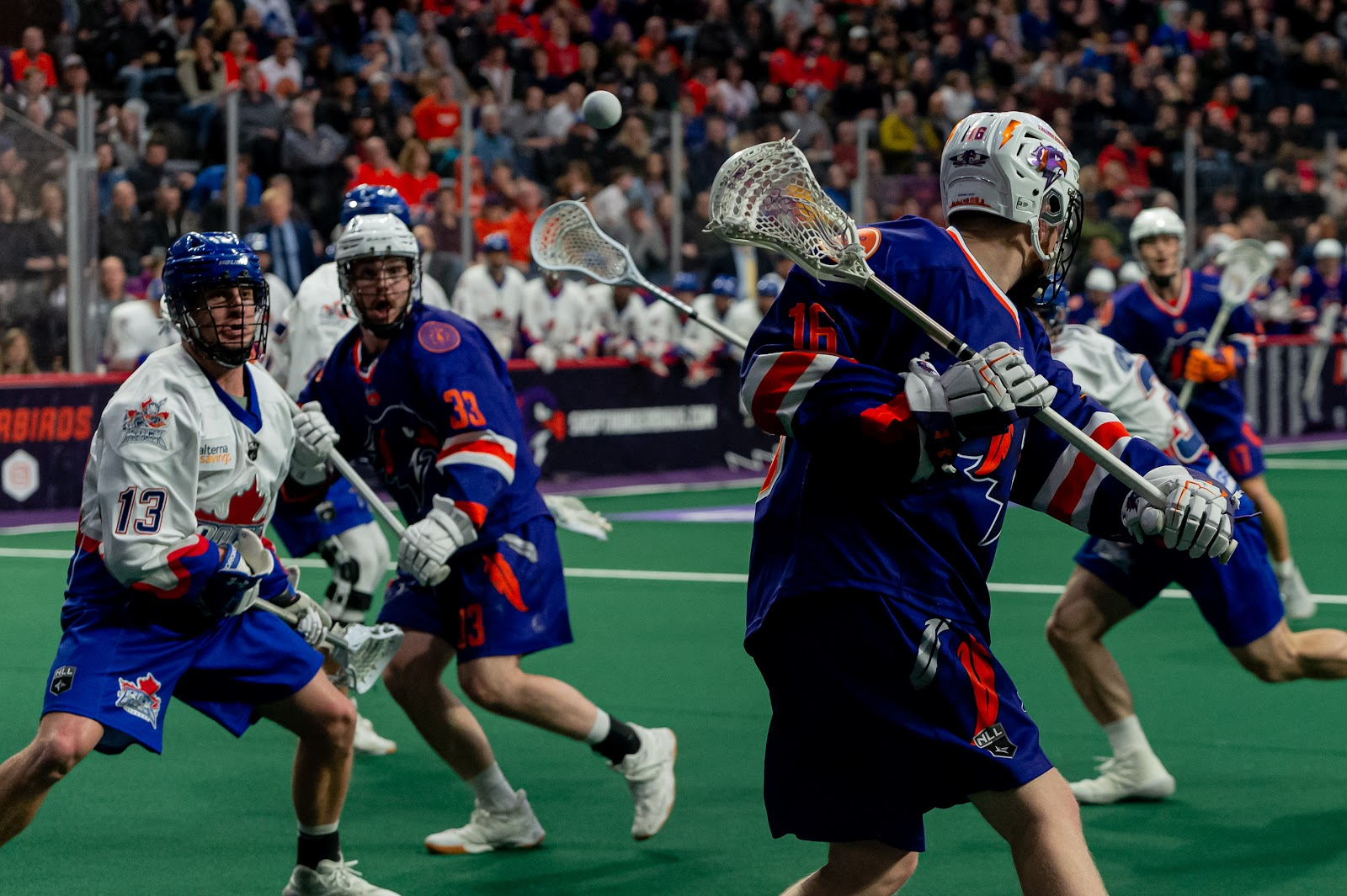 Pro lacrosse players in a game situation executing a give and go play