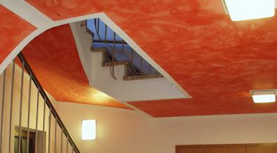 Photo: Die Deckengestaltung im Theater in Centrum prägt das gesamte Treppenhaus. Durch die Wolkigkeit der Decke öffnet sich der Raum nach oben. Durch die rote Farbgebung wirk das Treppenhaus warm und einladend. Das ist besonders im Winter notwendig das diese kleine Theater über keinen weiteren Windfang verfügt und das Treppenhaus auch Foyer und Garderobe ist.