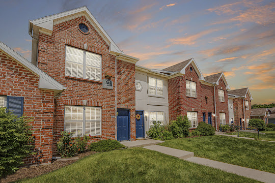 Maple Grove Villas apartment building with red brick at dusk
