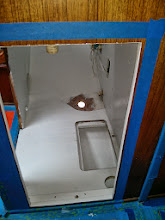 Photo: under sink area painted save for site of new sink drain through hull fitting