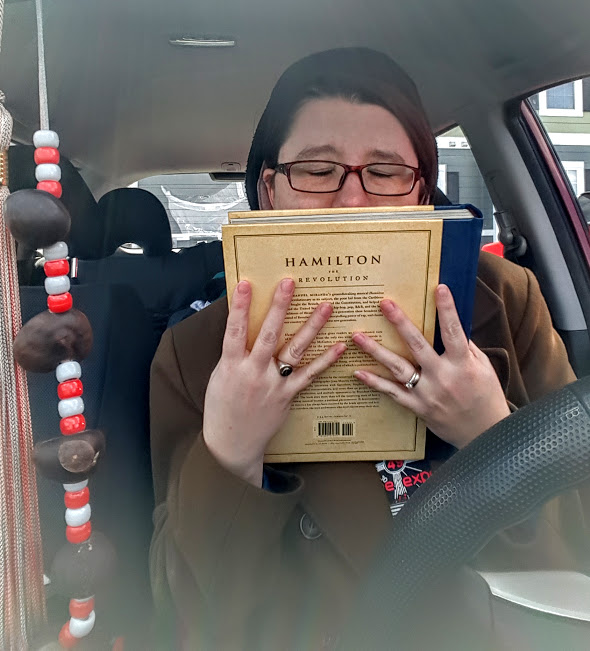 In my car, holding my copy of Hamilton: The Revolution to my face in pure joy of finally having it. It just arrived.