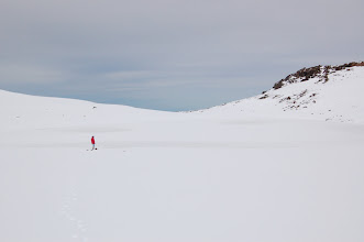 Photo: Lake Waiau comes into view, sort of, after we cross a small saddle at 13,200 ft. It's all frozen over and covered with snow. Marcia is standing at its edge. It covers about 1.8 acres with a max depth of about 10 ft.