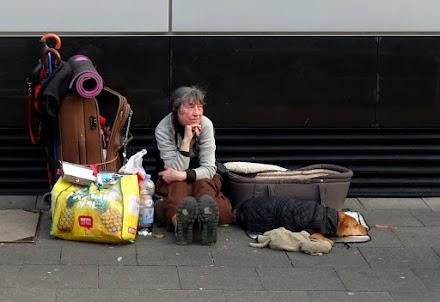 Hat alles dabei in Koffer, Tüten, Taschen – Obdachlose, sitzend mit Hund.