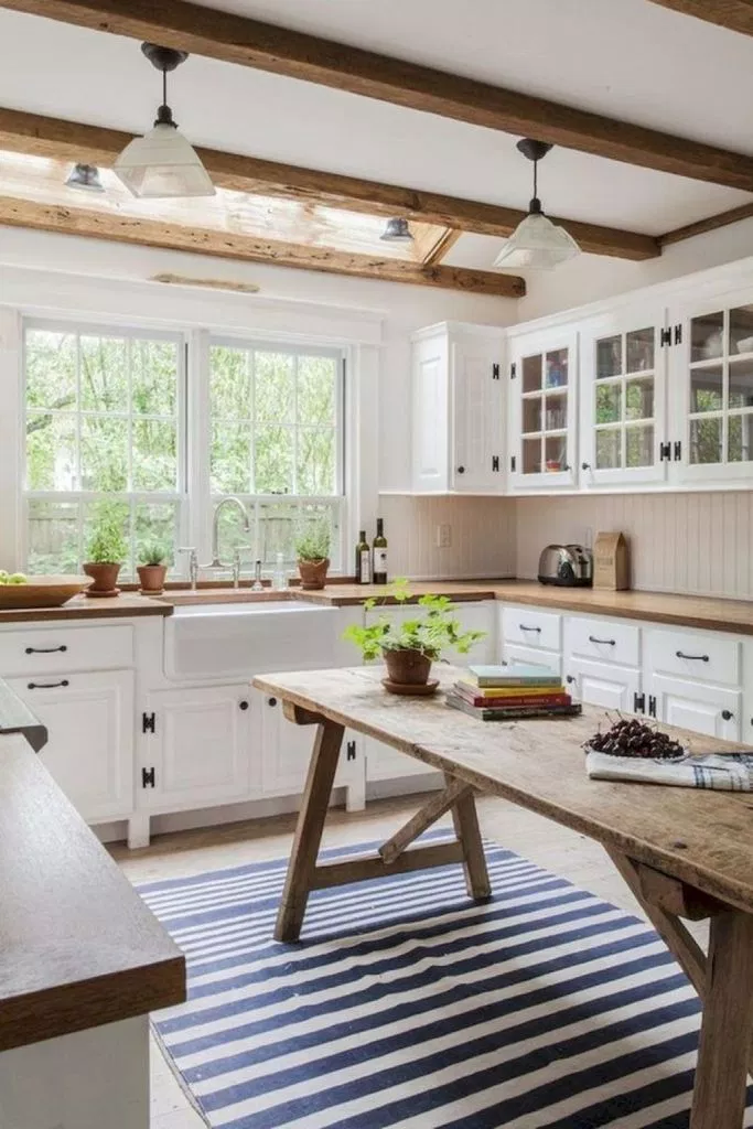 Large rustic country farmhouse kitchen with striped rug, white cabinets, black hardware, vintage wood table and porcelain farmhouse sink.