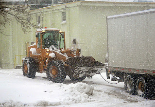 Photo: Front end loader pulls tractor trailer loose from snow