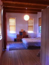 "Photo: This is the master bedroom. It has 12' high walls and a beautiful ""New Mexico"" style wood ceiling. The windows are 6' tall, and there are 7 of them plus the 8' tall French doors opposite the bed.  The closet area is open storage (IKEA) that leaves the volume of the room intact while still offering a separate dressing zone."