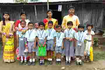 A photo of Sukla behind  nine students and three other adults. She wears a red outfit while the children wear matching light blue collared shirts and everyone faces the camera.