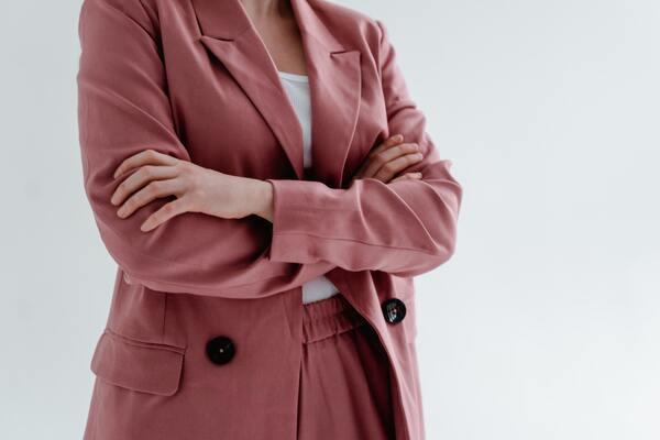Foto da metade do corpo de uma mulher com braços cruzados, vestindo um conjuntinho de terno da cor rosê escura.