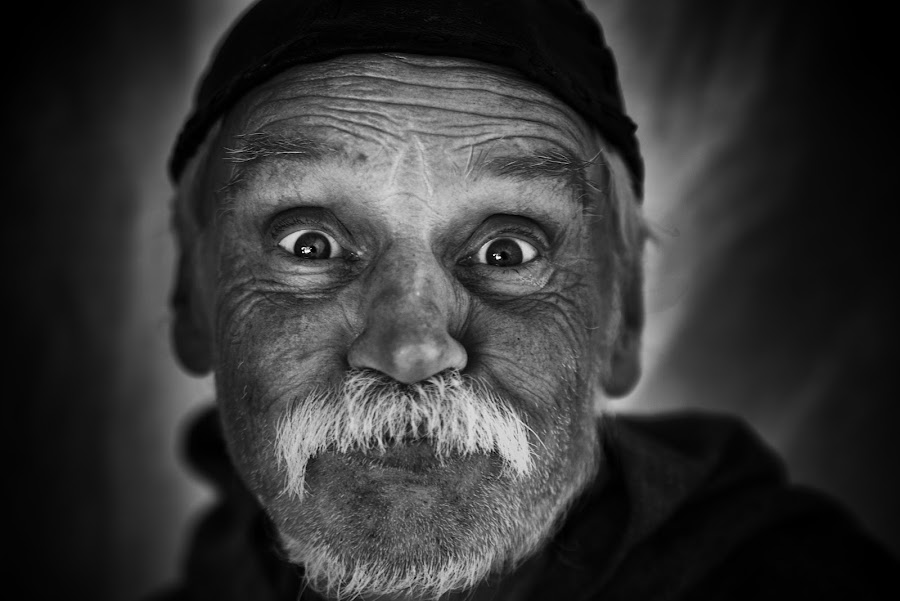 Gazing At The Camera by Marco Bertamé - Black & White Portraits & People ( gazing, close up, cap, beard, headshot, man, portrait, eyes, mustache )