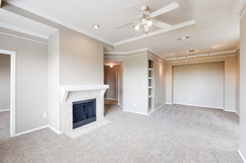 Spacious living area with white trim, a cozy fireplace, and plush carpet