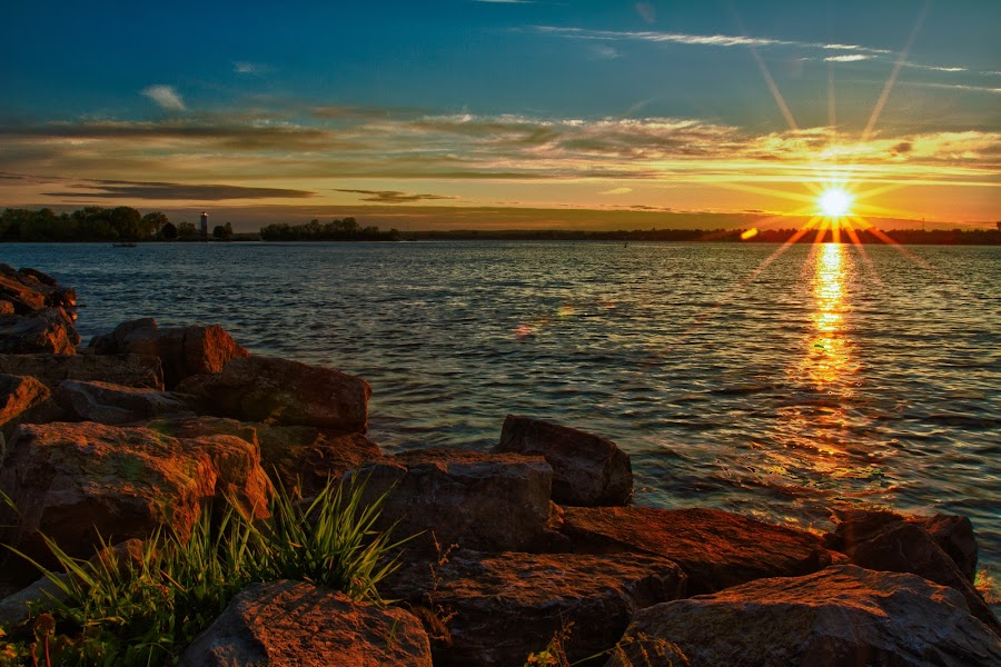 Lighthouse Point by Jerry Boyden - Landscapes Waterscapes ( harbor, st. lawrence river, boyden galleries, waterscape, rock, yellow, glow, landscape, ny, st. lawrence county, blue sky, nature, sunny, canon eos 7d, sunrays, shoreline, gold, rocks, clouds, st. lawrence, orange, colors, lighthouse, ogdensburg, great lakes, new york, sunlight, lighthouse point, rays, riverbank, boyden photography, blue, sunset, vibrance, summer, river bank, river )