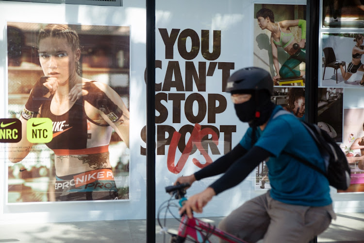 A cyclist wearing a mask passes a Nike store in Manila, the Philippines. Picture: GERIC CRUZ/BLOOMBERG