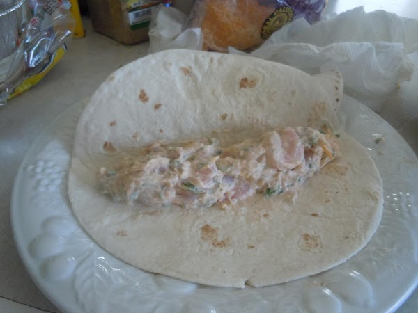 Place a tortilla on a plate and place mixture toward the edge and roll...