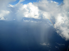 Photo: Complex cloud system east of Honolulu dropping rain in the center right and with a rainbow added on the top.