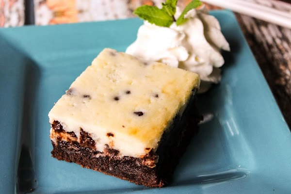 Cheesecake brownie on a blue plate with whipped cream.