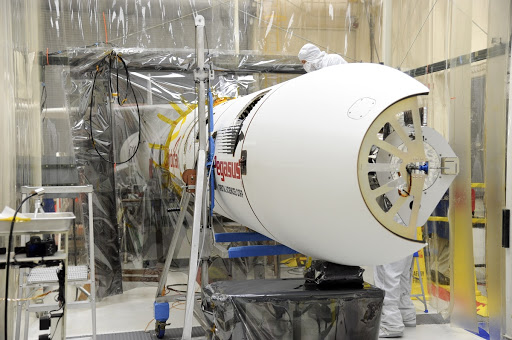 Orbital Sciences team members prepare to move the second half of the payload fairing before it is placed over NASA's IRIS spacecraft.