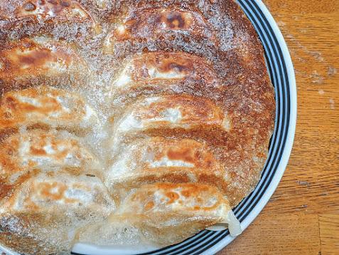 大阪王将餃子焼きあがって羽根を上にしてお皿に盛りつけた画像