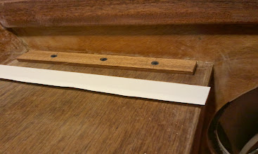 Photo: I used carpet tape to properly align the french cleat to the underside of the bench before fastening it down.