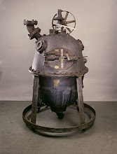 Photo: BAKELITE  The Original 'Bakelizer' - image from: National Museum of American History  In 1907, in the USA, Dr.Leo Baekeland, took two simple chemicals - phenol and formaldehyde - mixed and heated/pressurized them in an autoclave (which he called the 'Bakelizer' as pictured above). The result was an amber-coloured sticky resin that he called 'Bakelite' - the world's first entirely man-made/synthetic plastic - the first in a family of 'phenolic resins'. It could be produced in a limited range of quite bright colours in this state.  The problem with this plastic was that it was extremely brittle in its basic form and of little real use. Baekeland experimented further, and found it could be strengthend considerably by adding fillers - mostly using sawdust. However, this resulted in any colour turning a dark, muted hue.   It's main advantage over earlier plastics was that it could be moulded quickly and simply; it retained shape even when heated, pressurized or subjected to solvents - ie a thermoset plastic.