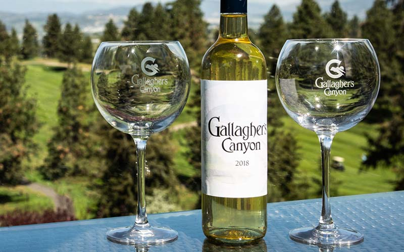A Gallagher's Canyon 2018 white wine bottle resting between two wine glasses overlooking the golf course.