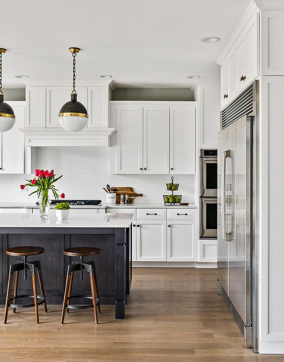 large contemporary kitchen with oak island and globe pendant lights. white shaker cabinets lighten up with space as well as a white brick backsplash and white wall paint.