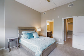 2A model bedroom with carpet, brick accent wall, and blue bed