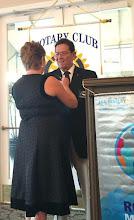 Photo: Kathy placing Rotary Club President pin on her husband Joe.