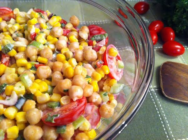 A Glass Bowl With A Mixture Of Chickpeas, Corns, And Tomatoes On A Green Table Mat With A Wooden Spoon And Whole Cherry Tomatoes.