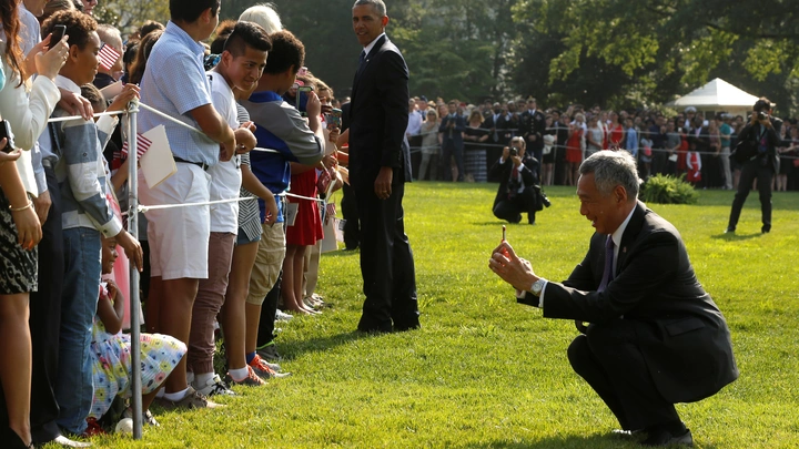 Singapore's Prime Minister Lee Hsien Loong photographed squatting on the White House Lawn while taking a picture.