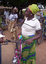 Photo: Agnes will buy a bike carrier to transport sacks of grain, (mostly millet, guinea corn or rice) which she buys locally and sells at the Hang market, about 8 miles away, round trip.  Without the bike she received from Village Bicycle Project, she could not move the grain to the busier markets.