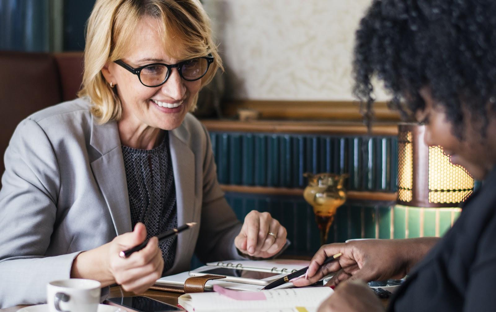 Duas mulheres conversando e anotando algo em um caderno.