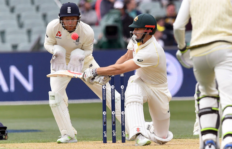 Australia's batsman Shaun Marsh (C) sweeps a ball as England wicketkeeper Jonny Bairstow (L) observes on the second day of the second Ashes cricket Test match in Adelaide in December 3, 2017.
