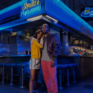 Man and woman with their arms around each other in front of a neon-lit bar