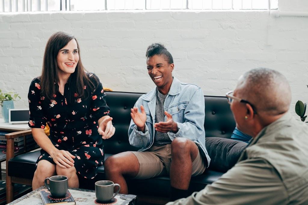 Tres personas reunidas casualmente toman café en un sofá.