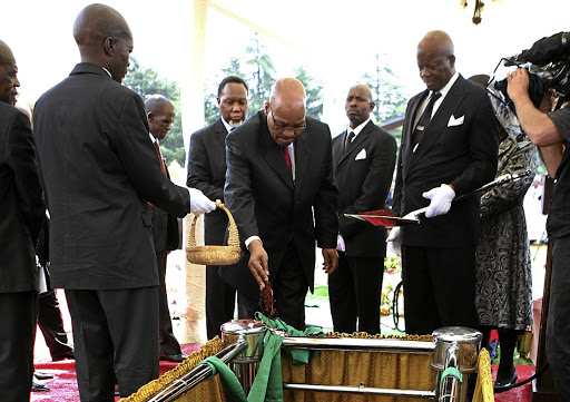 SOILED:  President Jacob Zuma drops soil onto the grave of veteran journalist Zwelakhe Sisulu at the West Park Cemetery in Johannesburg. Sisulu was imprisoned during apartheid for voicing opposition to the National Party.