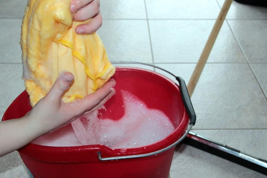 A person holding a rag over a mop bucket