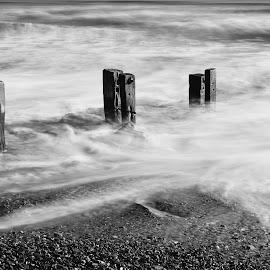 Youghal Strand Groynes 3/12/2019 by John Holmes - Black & White Landscapes ( waves, long exposure exposure, grouynes, seaweed, white water, wooden weather beaten, sand, strand, rocks, youghal, beach, wood, black and white, breakers )