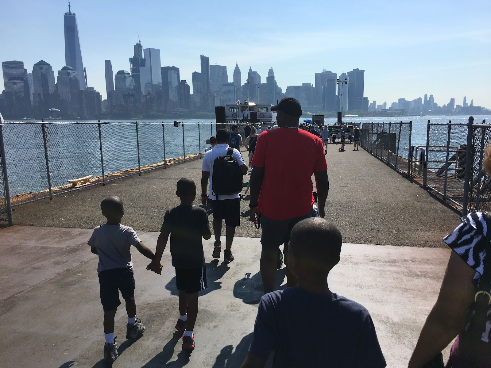 Family with three young boys walking on dock with NYC skyline in the background
