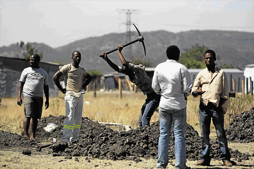 Nkaneng residents dig a grave during a site inspection by the Marikana commission of inquiry yesterday Picture: LAUREN MULLIGAN