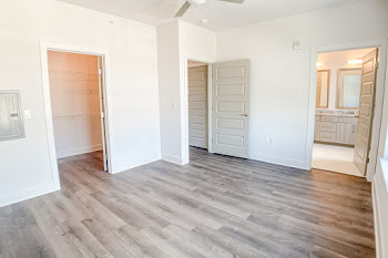 Bedroom with wood-inspired flooring, light walls, and ceiling fan