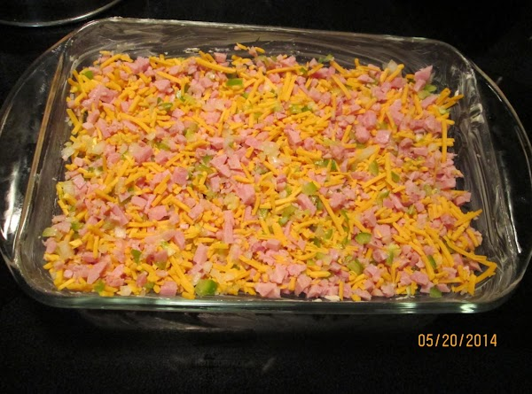 Place ham, cheese, onion and green pepper in the bottom of the prepared pan.