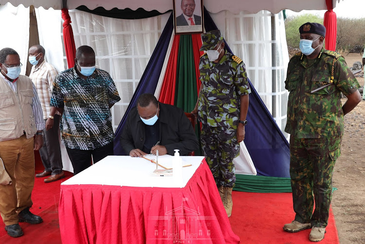 IG Hillary Mutyambai in the jungle uniform looks on as president Uhuru Kenyatta signs the visitor's book