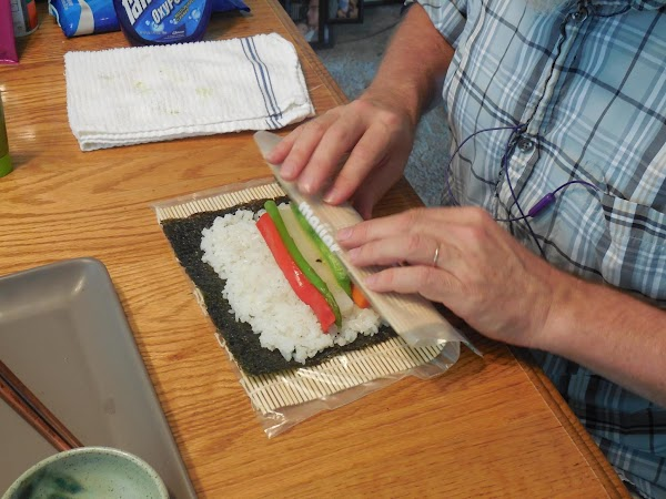 Then, using plastic wrap or sushi mat, lift edge of nori up and over...