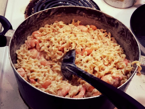 Add shrimp to the pasta, and then add the alfredo sauce and sour cream...