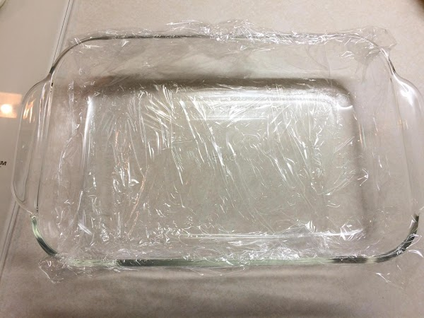 Line an 8 by 8 inch square baking dish with plastic wrap, leaving several...