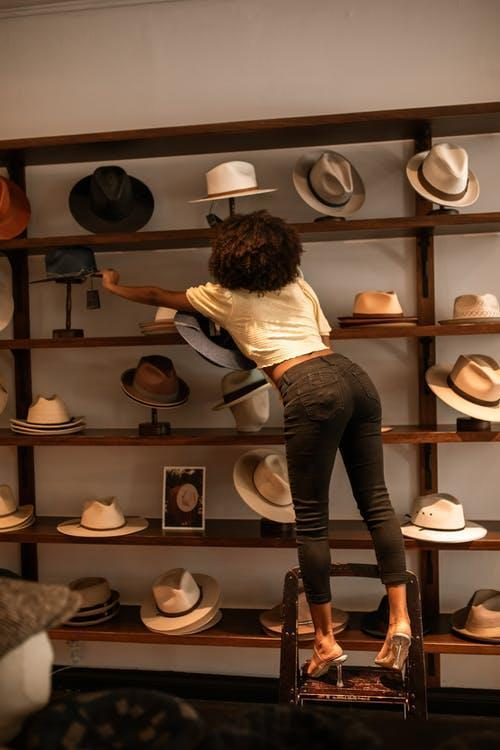 Woman in White Shirt and Blue Denim Jeans Standing in Front of Brown Wooden Shelf