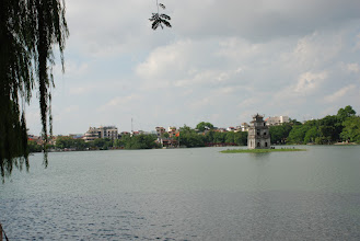 """Photo: Hoan Kiem Lake.  Hoan Kiem means """"Returned Sword"""". Legend has that, way back when in 1010, king Le Thai To, after a victorious battle against the then invader, had a cruise on the lake. A turtle (apparently a talking one) emerged and demanded the king to return the sword (which, in another part of the legend, had been lent to him by some sort of god) citing that the country were now in peace. The King did. Peace didn't stick for long but the name has remained since.  It's a very nice lake right in the middle of Hanoi with tons of people hanging out all the time, playing chess, reading or just looking at one another or at the foreign tourists. There are other things around the lake to see too, such as the Ngoc Son Pagoda, which is the house of a real deceased turtle (presumably the one that took the sword), the Water Puppet theater, Hanoi Opera House, Hanoi Moi newspaper, Hanoi Post Office...  There are indeed huge turtles in the lake. Some are believed to be hundreds of years old."""