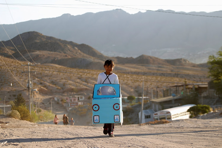 Jazmin, 9, carries a cardboard car to be used in a play in her school at Anapra neighborhood in Ciudad Juarez, Mexico.