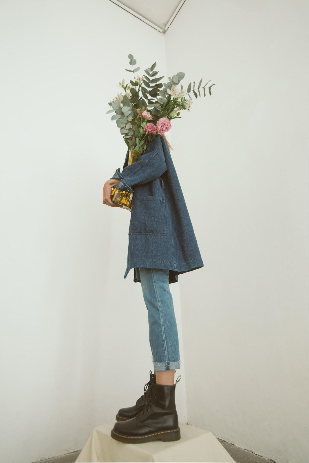 אישה מחזיקה זר פרחים שמסתיר את הפנים