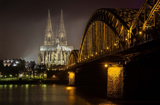 Cologne-cathedral-at-night-1 - The Cologne Cathedral rises in the night sky, framed by the Opera House, Railway Bridge and Rhine River in Cologne, Germany.  The cathedral, Kölner Dom in German, is one of the most iconic landmarks in Germany.